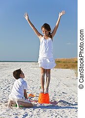 Two Children, Boy and Girl Making Sandcastles on Beach - Two...