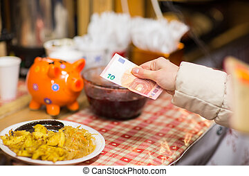 hand with money paying food at street market - food sale,...
