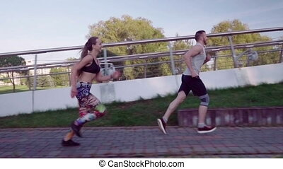 man and woman running in city park