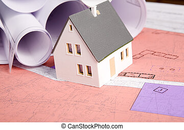 New real estate - Close-up of toy house model with rolled...