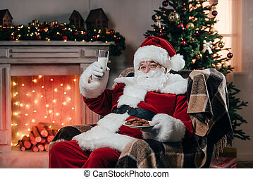 santa with cookies and milk - santa claus eating traditional...