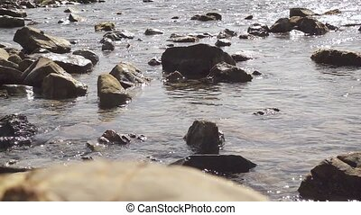 Many stones in the water in the sea slow mo - Many stones of...