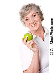Fruit diet - Portrait of aged female holding an apple and...