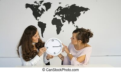 Two young girls twins with clock on the background of the...