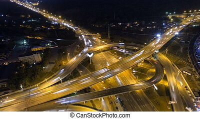 Traffic on freeway interchange. Aerial night view timelapse...