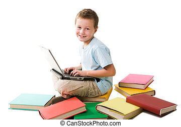 Happy schoolboy - Smart boy typing on laptop and looking at...