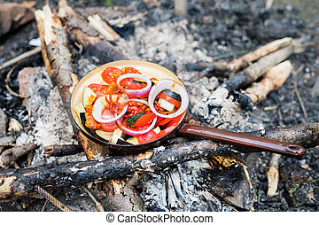 Cooking food on an open fire in nature. Vegetables on a...