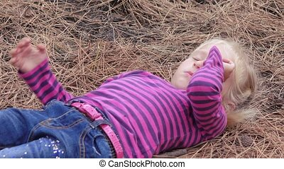 The child lies on a pine needle - On the pine needles the...
