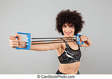 Smiling curly sports woman doing exercise with hand expander...