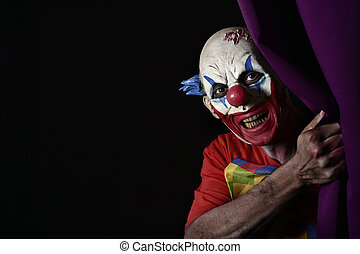 scary evil clown peering out from a stage curtain - closeup...