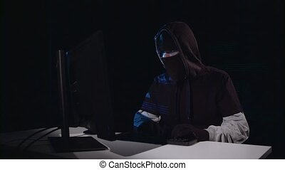 Terrorist copies information from the computer, on the table is a gun. Black background