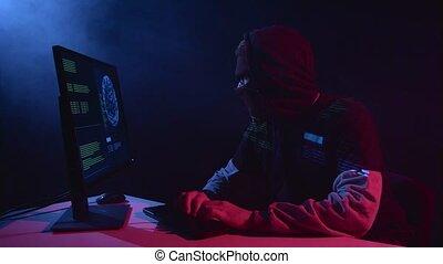 Man hacking computer sitting in a dark room. Black smoke...