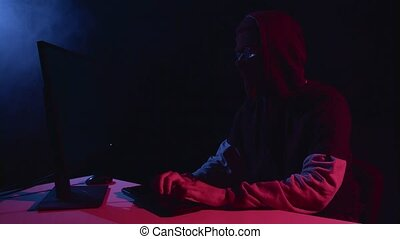 Spy hacking computer sitting in a dark room. Black smoke...