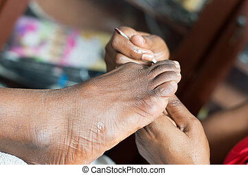 Closeu-up of a woman's foot. - Esthetician cleans the...