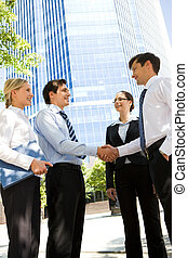 Greeting - Photo of business partners handshaking at meeting...