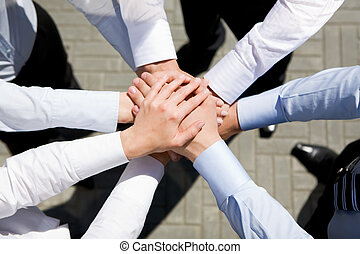 Strength - Above view of business partners hands on top of...