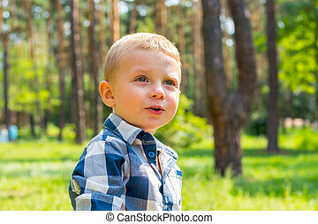 Little boy looks up at something interesting in the park on...