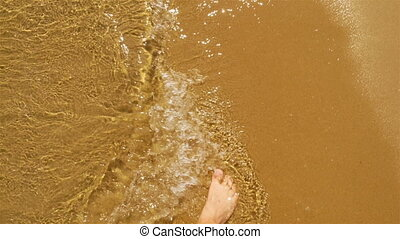 Man walking bare foot on sandy beach into sea wave, point of...