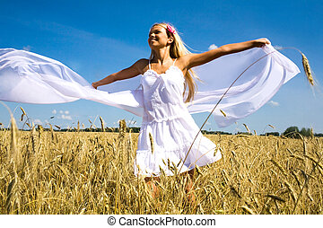 In the wheat field - Photo of glad girl holding white...