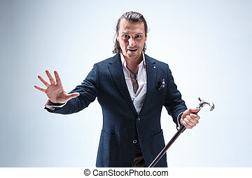 The mature barded man in a suit holding cane. - The mature...