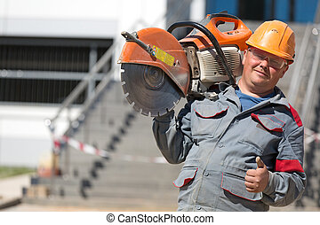 Construction worker with petrol disc cutter - Construction...