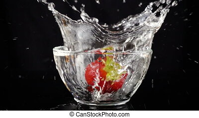 falling strawberry in glass bowl with water on black...
