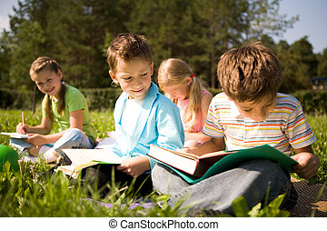 Reading outdoors - Portrait of cute kids reading books in...
