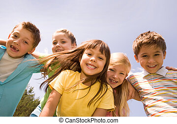 Joy - Portrait of happy children embracing each other and...