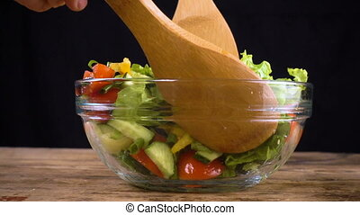 mixing salad ingredients in glass bowl, cooking for healthy...