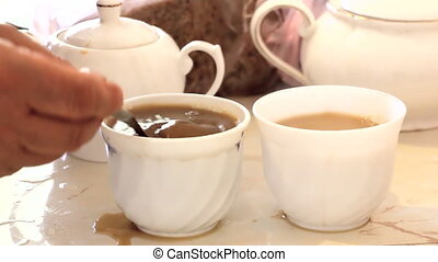 Pouring coffee with a spoon from a cup into another cup...