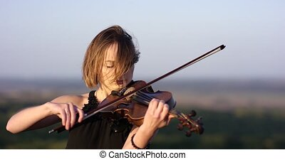 Girl violinist playing the violin on the roof with sky...
