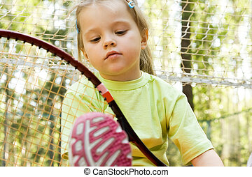 Sporty kid - Nice girl with tennis racket looking at it...