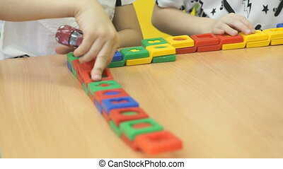 Children's hands play with colored blocks - Close up of the...