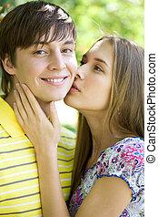 Tender kiss - Pretty girl kissing tenderly her boyfriend...
