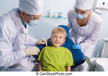 Child and dentists - Image of cute boy talking to dentist...