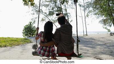 Couple On Swing Communication Back Rear View Taking Selfie...