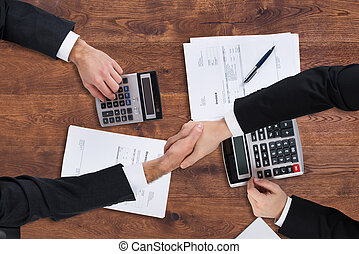 Elevated View Of Two Businesspeople Shaking Hands With...