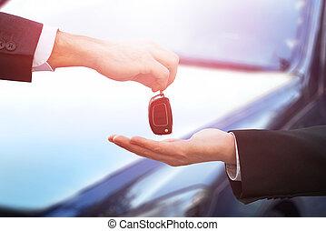 Car Dealer Giving Keys To Businessman - Cropped hands of car...