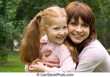 Mom and daughter - Portrait of happy woman embracing her...