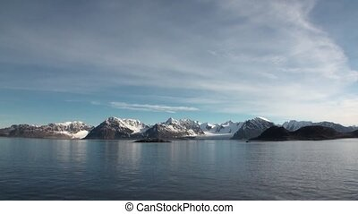 Desert coast and snowy mountains of Arctic Ocean in...