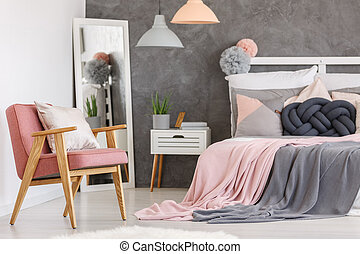 Pink chair in girls bedroom - White pillow on powder pink...