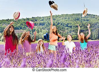 Joyful kids tossing up hats in lavender field - Joyful...