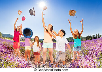 Happy kids tossing up hats over blue sky in summer - Group...