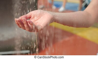 Womens hand covered in droplets of heavy rain in close-up,...