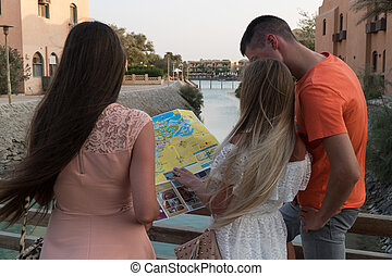 tourists with map reserch the city on sunset.