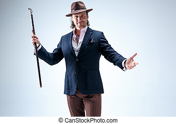 The mature man in a suit and hat holding cane. Isolated on a...