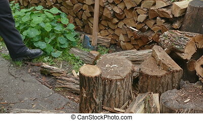 Firewood logs splitting using axe - Lumberjack chopping...