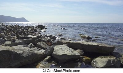 Small waves and ripples on the sea during the day. stony...
