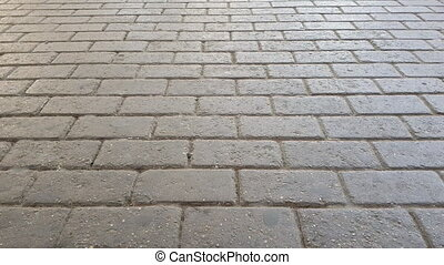 Man wearing jeans and leather shoes walking on cobblestone...