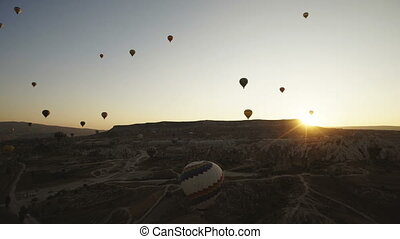 Colorful hot air balloons flying over Red valley at Cappadocia on sunset